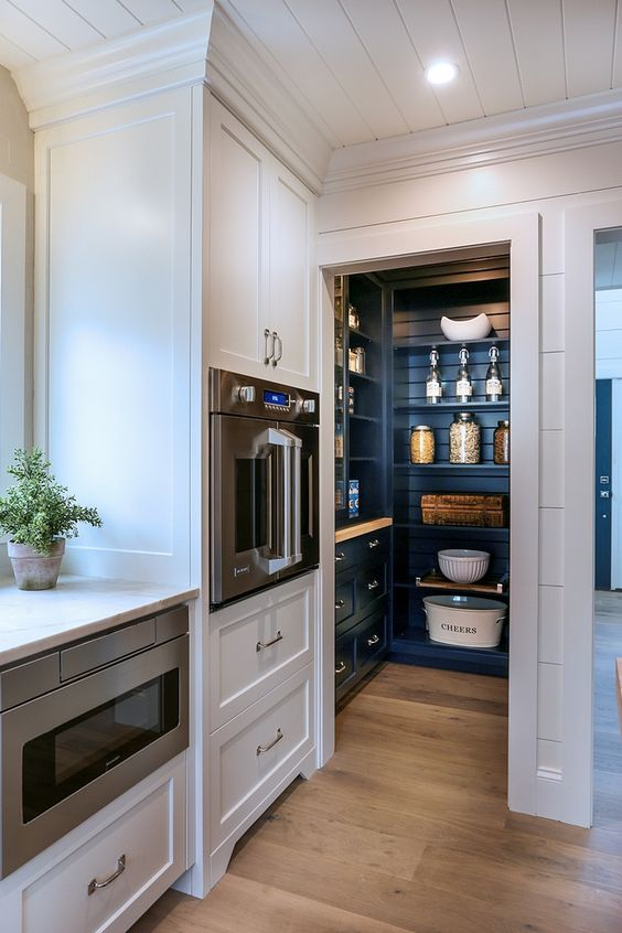 a small pantry integrated right into the kitchen and matching it in style but done in a contrasting navy color