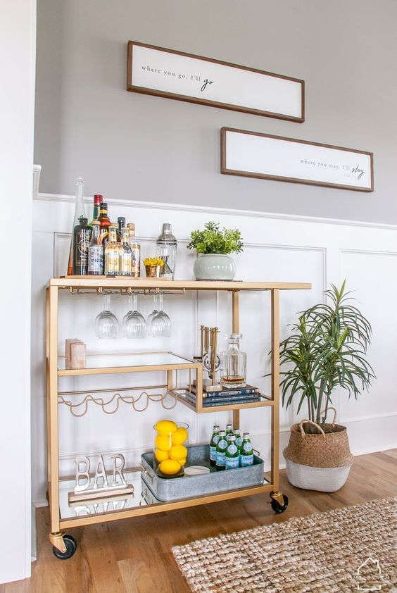 a stylish gold cart with various mirror shelves, stylish with a sign and some lemons ina  glass is a very chic idea