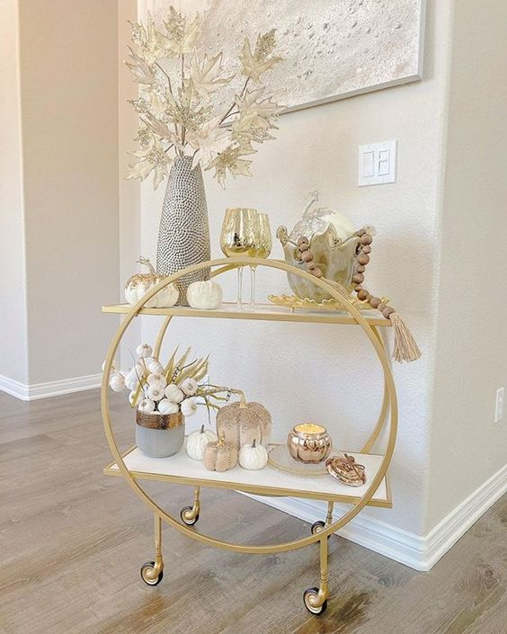 a lovely rounded gold bar cart on casters styled for the fall, with pumpkins, pampas grass, metallic leaves and wooden beads