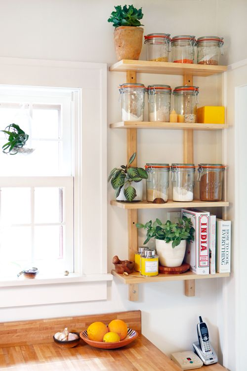 a small open shelf taking an awkward nook will let you store a lot of stuff without grabbing precious cabinet space
