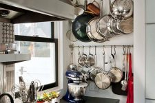 41 railings built into an awkward nook are great for hanging all the pans, teapots and pots without taking shelf space