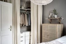 a Scandinavian bedroom done in neutrals, with a cane dresser and a small closet organized in the corner and hidden with curtains