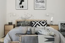 a Scandinavian bedroom with light stained furniture, printed bedding, a bench and a basket for storage plus a couple of artworks