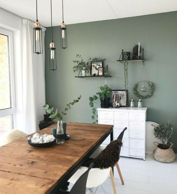 a Scandinavian dining room with a sage green accent wall, a rustic table, black and white chairs, pendant bulbs and open shelves