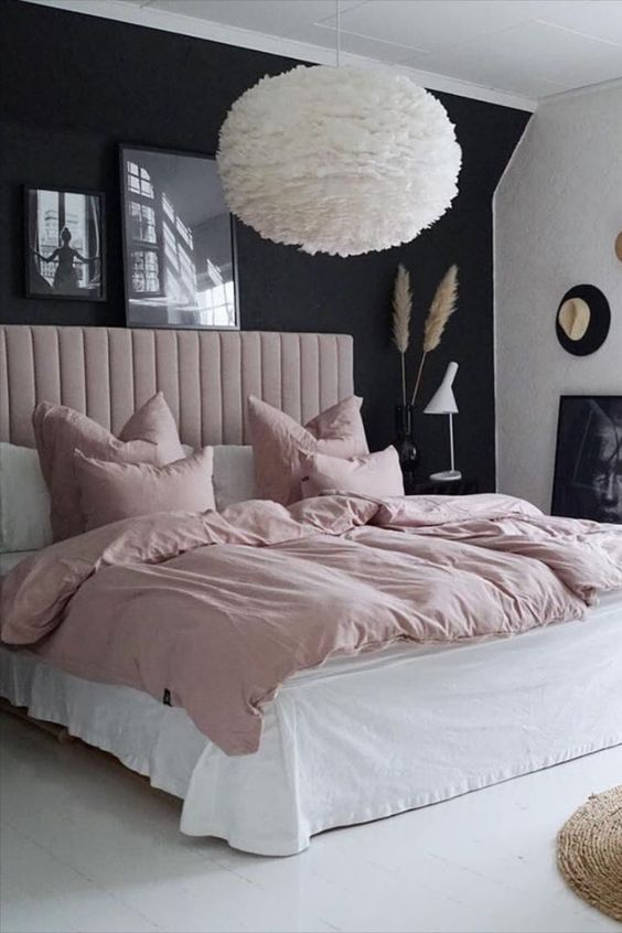 a beautiful and contrasting bedroom with a black accent wall, a blush upholstered bed and blush bedding, a fluffy pendant lamp and a mini gallery wall