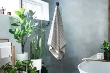a beautiful bathroom done with concrete, an oval tub, potted plants and a towel stand is a chic and cool space