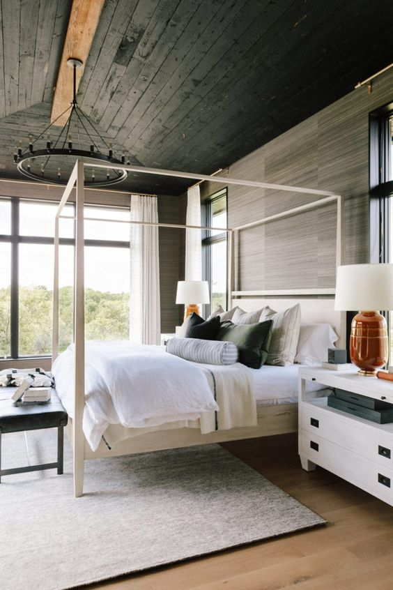 a beautiful bedroom with a black planked ceiling and wood-inspired wallpaper, a neutral canopy bed, white nightstands and creative bedding