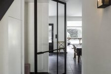 a beautiful black metal frame and glass pivot inner door with a small handle bar is a fantastic solution with plenty of style
