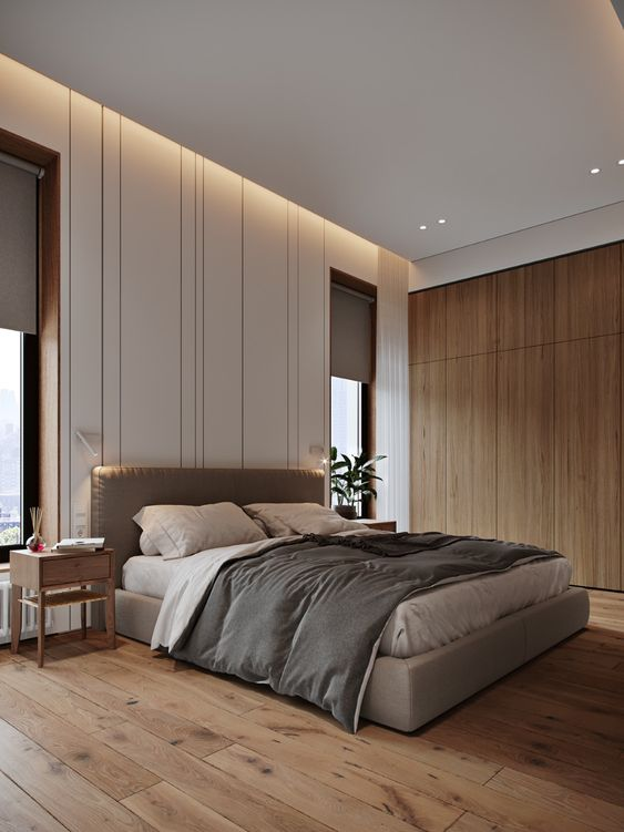 a beautiful contemporary bedroom with built-in lights, a grey upholstered bed, grey bedding and curtains, wooden nightstands and a sleek storage unit