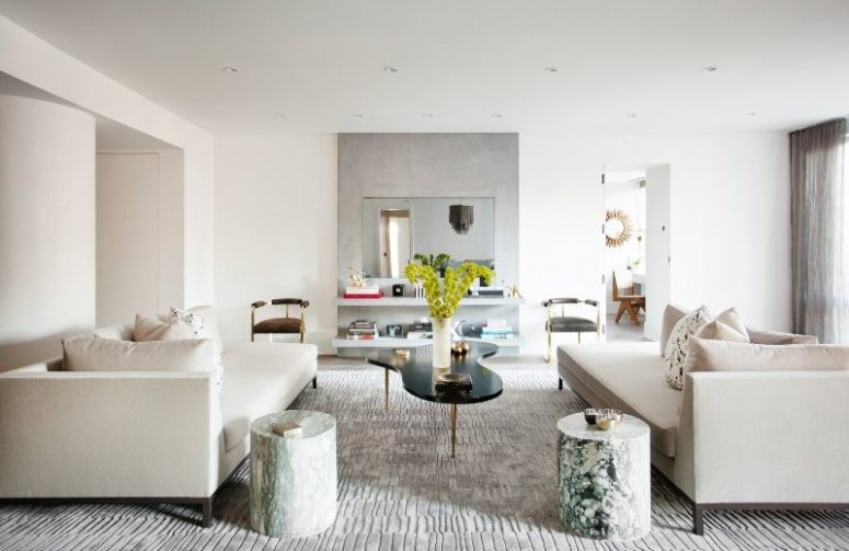 a beautiful contemporary living room with floating shelves and a mirror, creamy sofas, stone side tables, a catchy coffee table and lots of accessories