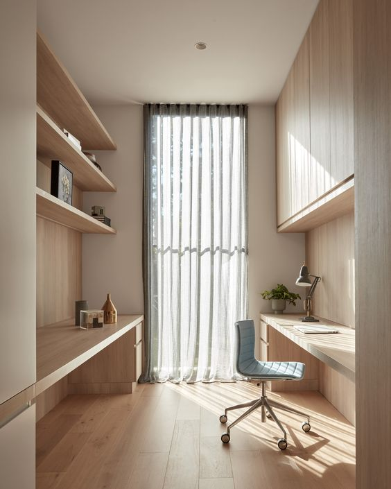 a beautiful home office completely clad with light stained wood, with open shelves and sleek storage units, built-in desks and a large window