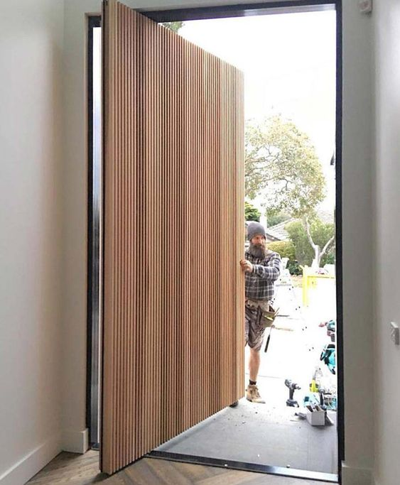 a beautiful light-stained wood slab pivot door is a lovely idea for a contemporary home and it looks amazingly clean and sleek