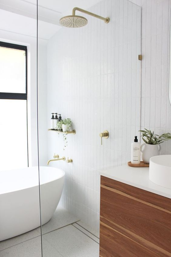 a beautiful minimalist bathroom with white skinny tiles, a chic tub, gold appliances, a wooden vanity and potted greenery is chic