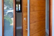 a beautiful modern rich-stained pivot wooden door with a frosted glass insert is a very cool idea for a modern entrance