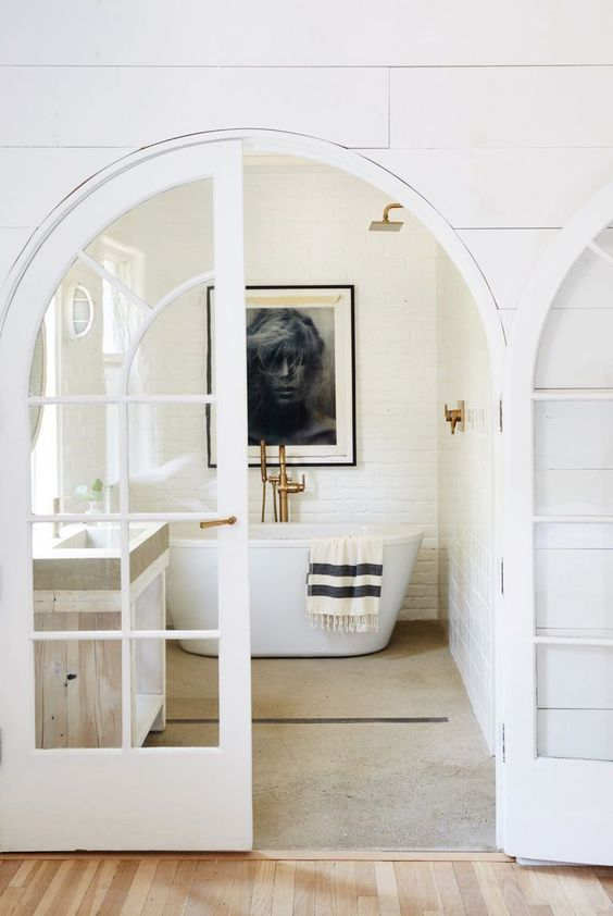a beautiful neutral bathroom with a brick accent wall, arched French doors and neutral furniture is a very chic and cool idea