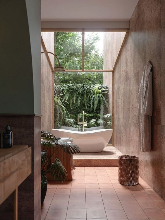 a biophilic bathroom clad with terracotta tiles, with a wooden vanity and a tree stump and a living wall is a gorgeous space
