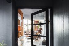 a black frame and glass pivot entrance door looks amazing with geometric tiles on the floor and makes a statement