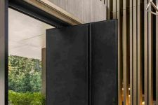 a black metal pivot door with a line for an accent and a handle is a gorgeous idea for a luxurious space