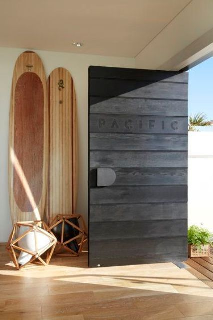 a black stained wooden pivot door with a metal knob is a gorgeous idea for many spaces and adds a beach feel with the inscription