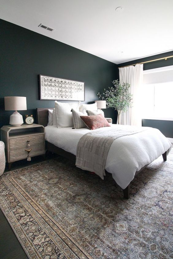 a boho master bedroom with dark green walls, a cool bed and eye catchy nightstands, a potted plant and printed textiles