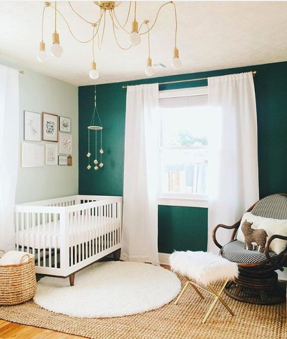 a boho modern nursery with a green accent wall, a white crib and a dark stained chair, neutral textiles, a whimsy chandelier and a basket for storage