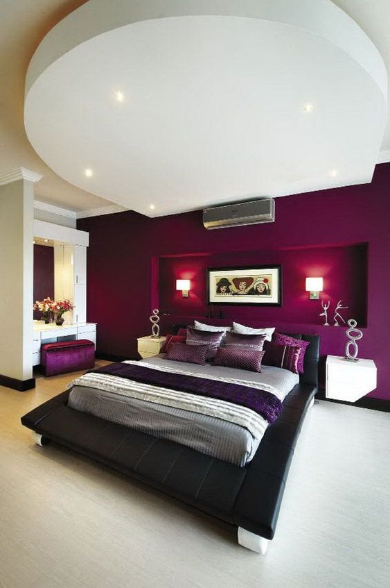 a bold and refined bedroom with a purple accent wall with a niche for lamps, a black bed, a chic vanity space and built-in lights