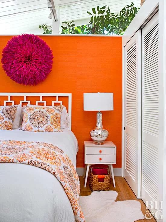 a bold bedroom with an orange wallpaper accent wall, white mid-century modern furniture, a fuchsia decoration and a wardrobe with shutter doors