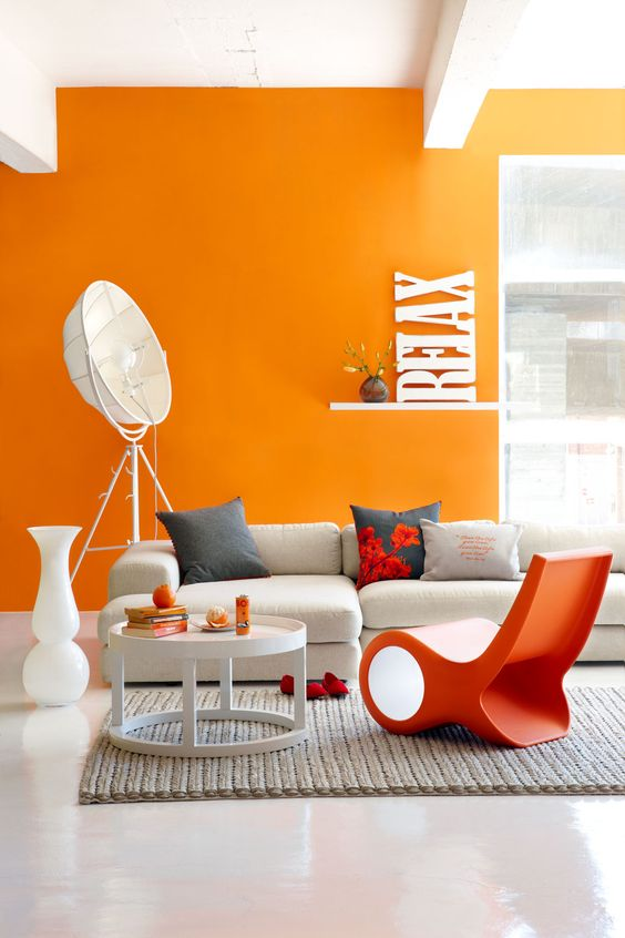 a bold contemporary living room with an orange accent wall, a white corner sofa, an orange chair, a round table, some quirky lamps