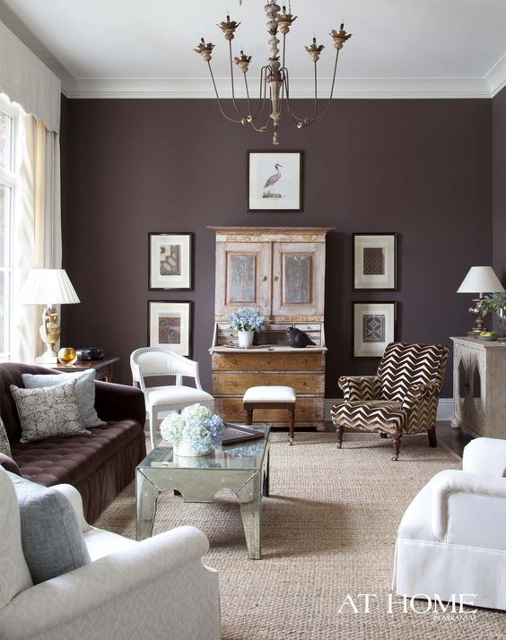 a bold eclectic living room with a deep purple accent wall and a matching sofa, a gallery wall, a refined chandelier, a mirror coffee table and a printed chair