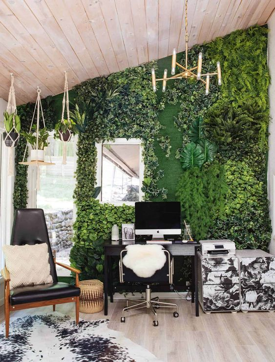 a bold home office with a faux living wall with much texture, suspended pots with plants, black and white furniture is a cool space