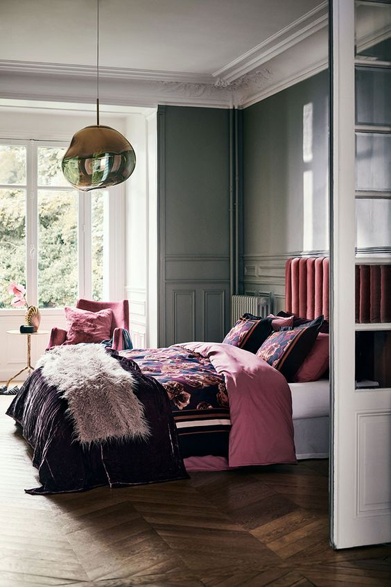 a bold refined bedroom with grey molding walls, a pink upholstered bed and a pink chair, bright floral bedding and a dreamy pendant lamp