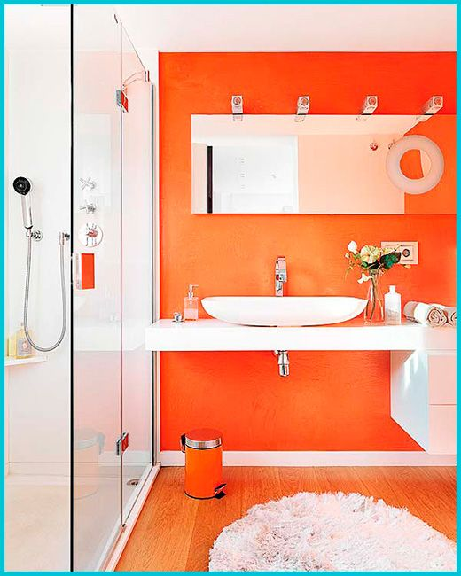 a bright bathroom with an orange accent wall and all white everything, with an orange trash can and a long mirror is wow