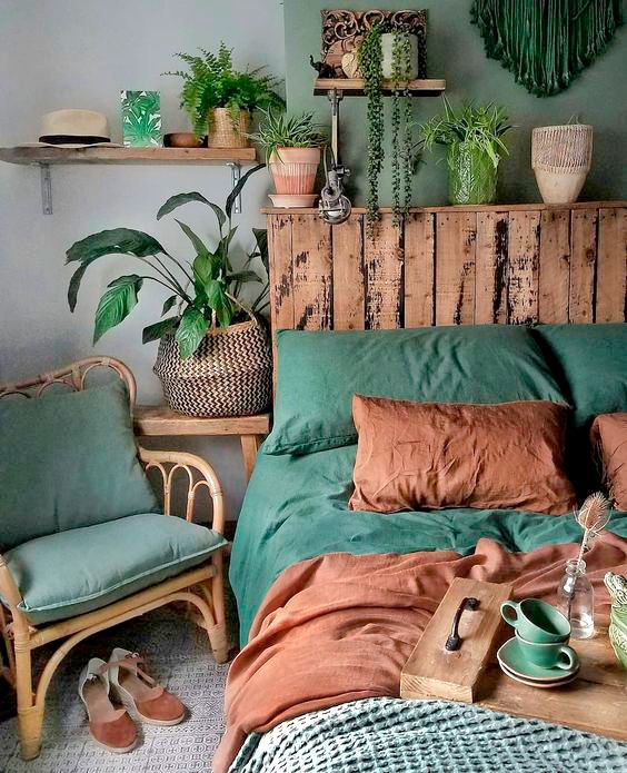 a bright boho bedroom done in green and rust shades, with lots of potted plants, a rattan chair and a bed with a pallet headboard