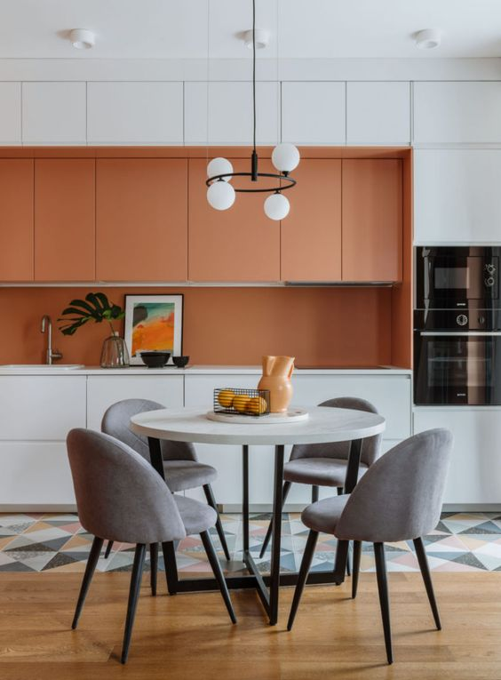 a bright contemporary kitchen with orange and white sleek cabinets, an orange backsplash and white countertops, a geo tile floor
