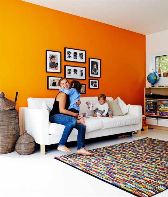 a bright living room with an orange accent wall, a white sofa, open storage units and a colorful rug plus a gallery wall with family pics