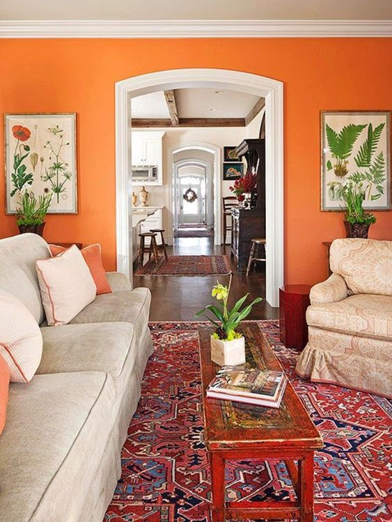 a bright living room with an orange accent wall, neutral vintage furniture, a printed rug, a low inlaid coffee table and botanical posters