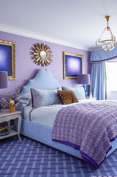 a bright purple bedroom with a lilac accent wall, gold details, a pretty pendant lamp, some refined nightstands and a sunburst mirror