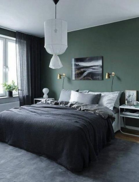 a chic bedroom with a green accent wall, a bed and cool bent nightstands, a pendant lamp and a bold artwork plus moody bedding