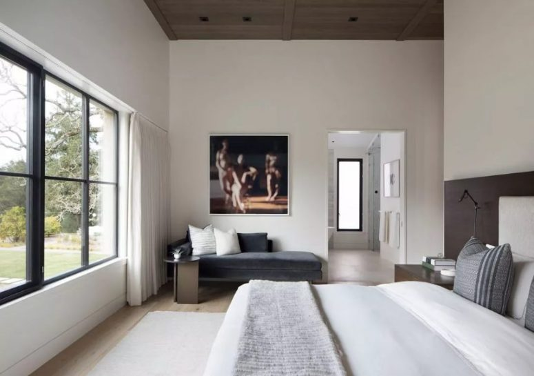a chic contemporary bedroom with a wooden ceiling, a neutral upholstered bed with neutral bedding, a graphite grey upholstered daybed and a small side table plus a lovely artwork