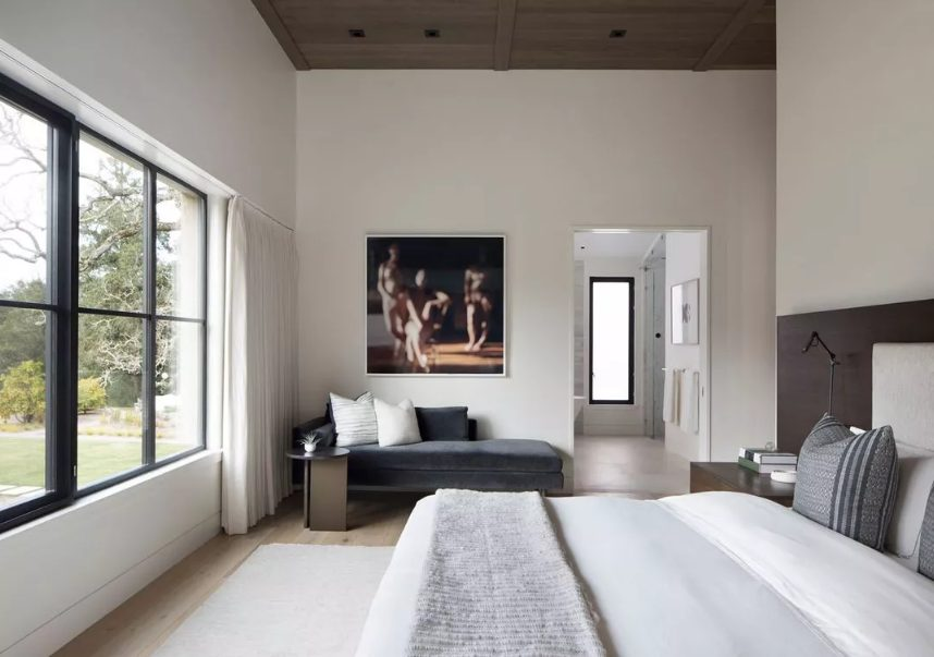 a neutral bedroom with a stylish wooden ceiling