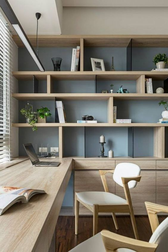 a chic contemporary home office with a storage unit that takes a whole wall, with open and closed storage compartments, a built-in desk and chic modern chairs