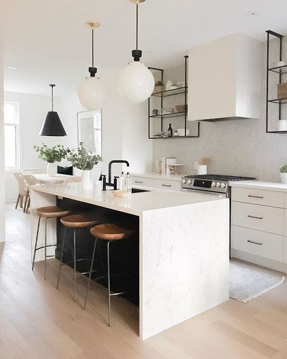 a chic contemporary kitchen with elegant white cabinets, a white tile backsplash, a black kitchen island with a white stone countertop and pendant lamps
