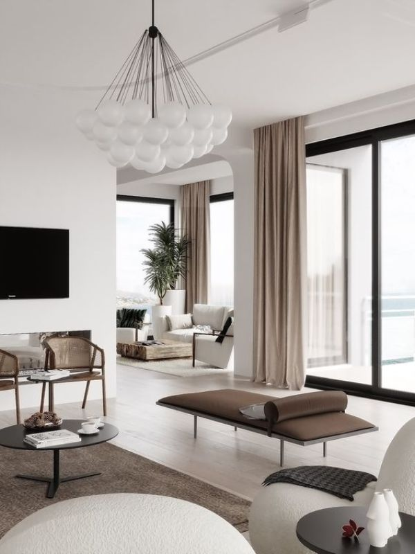 a chic contemporary living room with a chocolate brown daybed, rattan chairs, leather chairs, a round coffee table and bubble chandelier