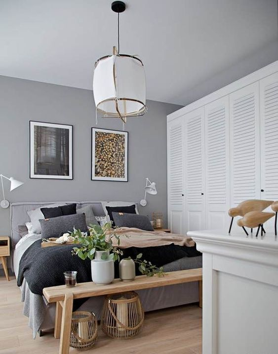 a chic modern bedroom done in greys, with stained furniture, a large shutter door closet right here and a catchy pendant lamp