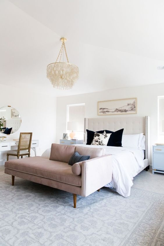 a chic modern bedroom with an upholstered neutral bed, a pink daubed, printed bedding, a tassel chandelier and a vanity space