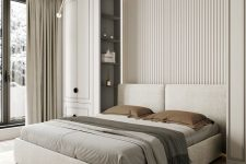 a clean contemporary bedroom with a neutral slab accent wall, an upholstered bed, two tall storage units, built-in lights and pendant lamps