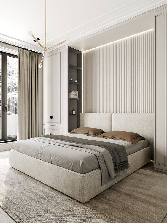 a clean contemporary bedroom with a neutral slab accent wall, an upholstered bed, two tall storage units, built in lights and pendant lamps