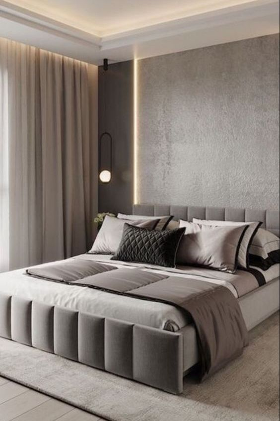 a clean contemporary bedroom with grey walls, built-in lights on the ceiling, a large upholstered bed and neutral textiles is a lovely space
