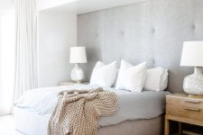 a clean neutral contemporary bedroom with a grey upholstered wall and an upholstered bed that matches, neutral textiles and a large rug