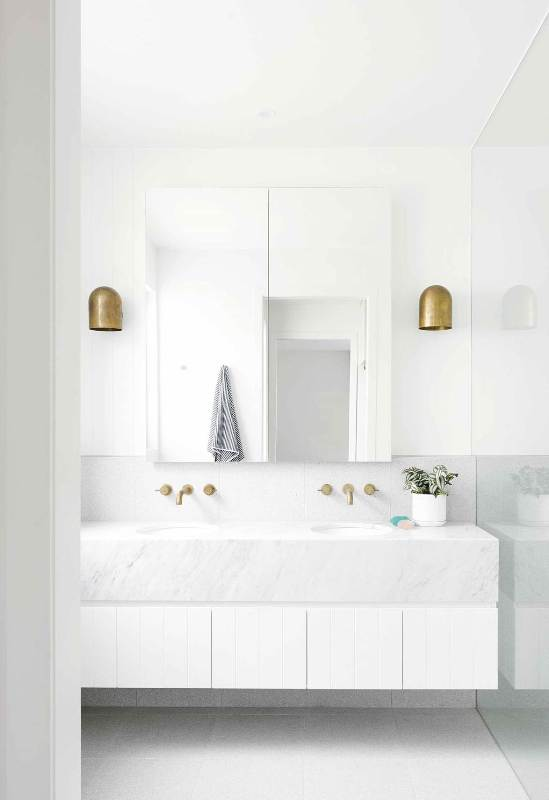 a clean white bathroom with a large mirror, a large floating vanity clad with marble and tiles and brass fixtures is cool